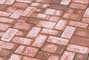 White efflorescence on a red block paved surface